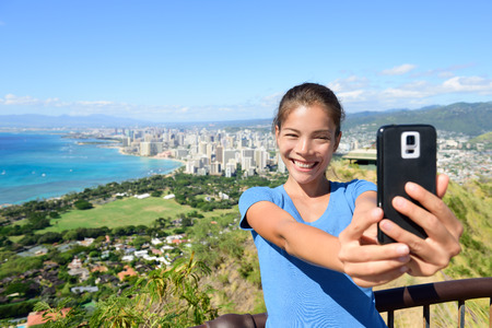diamond head: Hawaii tourist taking selfie photo of Honolulu and Waikiki beach using smartphone. Woman on hike visiting famous viewpoint lookout in Diamond Head State Monument and park, Oahu, Hawaii, USA. Stock Photo