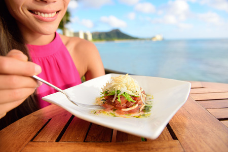 ahi: Tuna tartare. Raw ahi, Hawaiian food. Woman eating dish on Waikiki, Oahu, Hawaii.
