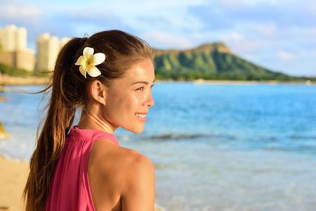 hawaii sunset: Hawaiian beach woman on Waikiki - beautiful biracial Asian Caucasian girl brunette relaxing and enjoying sun. Oahu, Hawaii, USA.