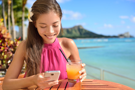 Woman using smartphone at beach bar drinking Mai tai Hawaiian cocktails having fun. Close up of woman holding alcoholic drink in Waikiki beach, Honolulu, Oahu, Hawaii, USA. Banque d'images