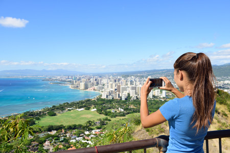 diamond head: Hawaii tourist taking photo of Honolulu and Waikiki beach using smartphone camera. Woman tourist on hike visiting famous viewpoint lookout in Diamond Head State Monument and park, Oahu, Hawaii, USA.