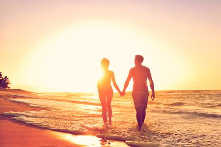 로맨스: 해변 일몰 사랑에 낭만적 인 신혼 부부. 여행 휴일 휴가 동안 바다 일몰을 즐기는 신혼 행복 한 젊은 커플 손을 잡고.