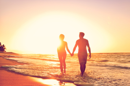 Honeymoon couple romantic in love at beach sunset. Newlywed happy young couple holding hands enjoying ocean sunset during travel holidays vacation getaway. Stock Photo