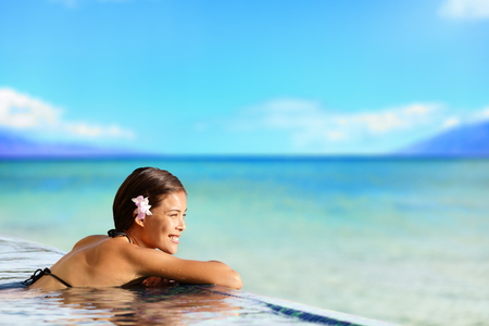 chillen: Entspannende Frau in Luxus-Hotel-Pool auf Urlaub Urlaubsreisen. Asiatische junge weibliche Person genießen im Pool Spa im Hotel-Resort in einem exotischen Paradies Wochenende.