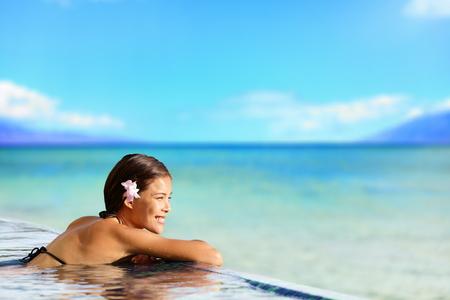 flores exoticas: Mujer de relajación en la piscina del hotel de lujo en viajes vacaciones vacaciones. Persona de sexo femenino joven asiática que disfruta en el balneario de la piscina en el complejo de hotel en una escapada paraíso exótico.