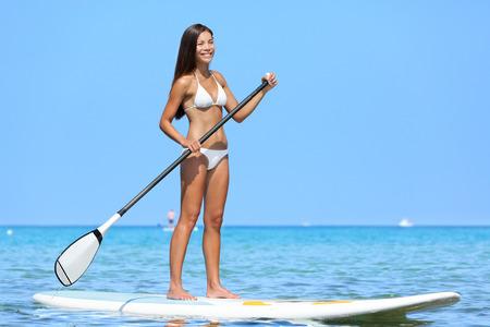 hawaiana: SUP Stand up paddle board mujer paddleboarding en Hawaii de pie feliz en paddleboard en el agua azul. Modelo joven birracial asi�tica mujeres de raza cauc�sica en la playa hawaiana en verano viaje vacaciones vacaciones.