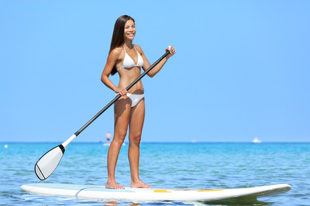 SUP Stand up paddle board woman paddleboarding on Hawaii standing happy on paddleboard on blue water. Young biracial Asian Caucasian female model on Hawaiian beach on summer holidays vacation travel.