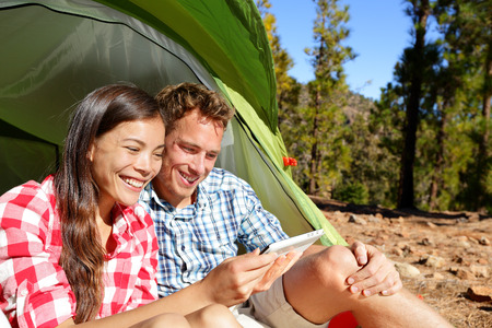 Camping couple in tent using smartphone or small tablet looking at pictures photos. Campers smiling happy outdoors in forest. Happy multiracial couple having fun outdoor. Asian woman, Caucasian man photo