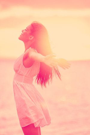 Freedom - Free happy serene woman enjoying sunset. Beautiful woman in dress embracing the golden sunshine glow of sunset with arms outspread and face raised in sky enjoying peace, serenity in nature Stock Photo
