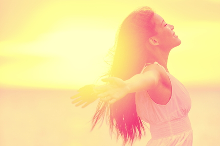 Happiness - Free happy woman enjoying sunset. Beautiful woman in white dress embracing the golden sunshine glow of sunset with arms outspread and face raised in sky enjoying peace, serenity in nature Standard-Bild