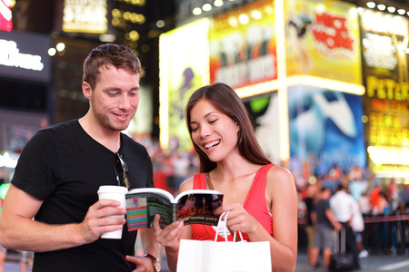 guidebook: People in New York - happy couple on Times Square. Shopping young couple reading guidebook drinking coffee. Beautiful young couple having fun in city, Manhattan, USA. Asian woman, Caucasian man.