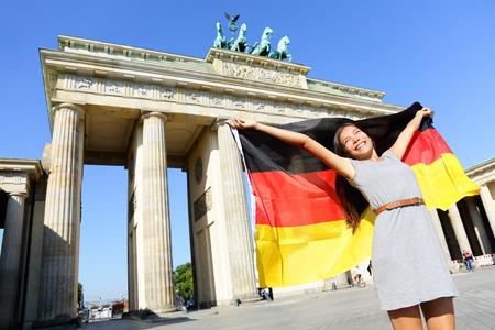 Duitse vlag - Vrouw gelukkig in Berlijn Brandenburger Tor gejuich vieren wapperende vlag van Berlin Brandenburg Gate, Duitsland. Vrolijke opgewonden multiraciale vrouw in Duitsland reizen concept. Stockfoto