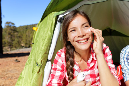 Camping woman applying sunscreen sun cream sunblock suntan lotion in tent smiling happy outdoors in forest. Happy biracial Asian Caucasian girl living healthy active lifestyle.