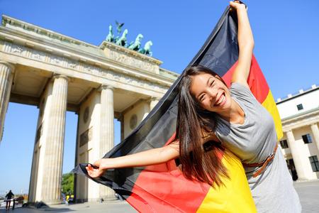 bandera alemania: Bandera alemana - mujer feliz en Berl�n, Alemania, la Puerta de Brandenburgo animando la celebraci�n de bandera ondeando por Brandenburger Tor. Mujer multirracial emocionada alegre en concepto de viajes de Alemania. Foto de archivo