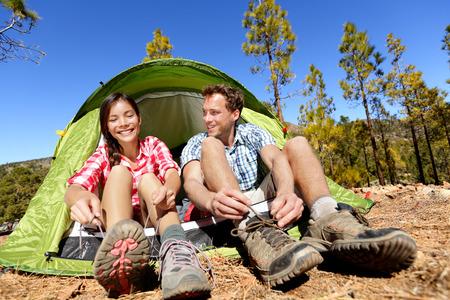 Camping mensen zetten op wandelschoenen door tent. Campers koppelverkoop veters klaar voor wandeling. Aziatische vrouw en blanke man woont leuke actieve levensstijl buiten.