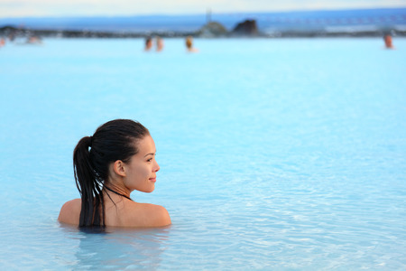 calor: Spa geotérmico. Mujer que se relaja en la piscina de aguas termales en Islandia. Muchacha que disfruta de baño en una atracción turística de Islandia laguna azul agua. Foto de archivo