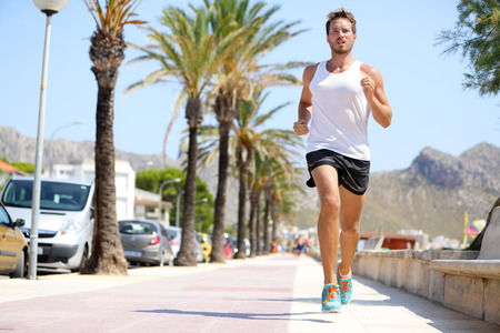 jogging in nature: Fit male runner running outside on boardwalk. Young man model training fitness jogging on Mallorca beach city outdoors in summer sun.  Stock Photo