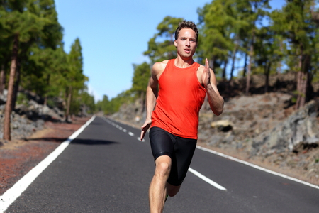 sprint de Sport jeune athlète à l'extérieur pour la formation marathon de beau mâle. Fitness model dans la vingtaine en cours d'exécution sur la route dans la nature de l'été. Banque d'images