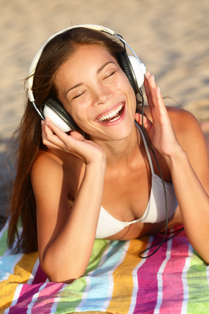 girl with towel: Woman listening to music with headphones at beach. Young Asian girl relaxing during summer holidays lying down with towel on golden sand enjoying her vacations singing happy. Stock Photo