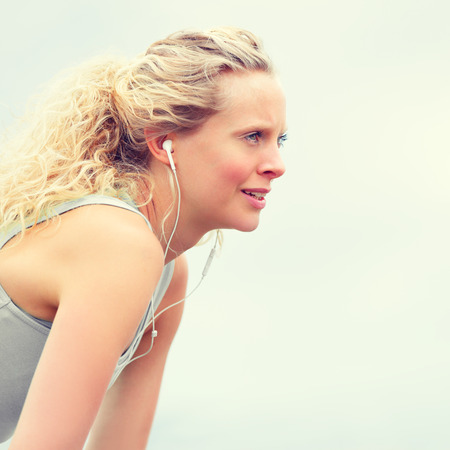 active listening: Active young fit woman exercising with earphones. Young fitness woman taking a break outside in summer fitness workout. Beautiful caucasian female model in running lifestyle listening to music.