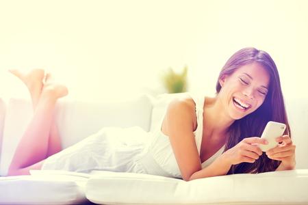 Smartphone vrouw die app op mobiele telefoon glimlachen gelukkig. Mooie multiculturele jonge vrouw model met behulp van slimme telefoon sms versturen van SMS-bericht liggend op de bank. Gemengd ras Aziatische blanke meisje. Stockfoto