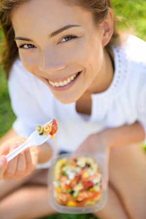 Woman eating gluten free pasta salad. Portrait of girl eating lunch takeaway in park outdoors. Biracial Asian Caucasian female model in her twenties smiling happy looking at camera.