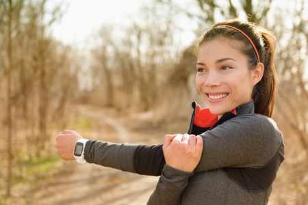 Fitness woman stretching arms with smartwatch before running or cardio workout. Happy Asian girl doing warm-up before jogging with heart rate monitor in outdoor park during autumn.
