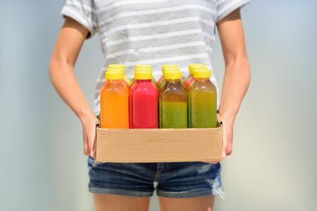 Femme tenant boîte de livraison de bouteilles de jus de fruits et de légumes fraîchement pressées à froid. Gros plan de la personne de sexe féminin portant jus premières organiques. Jus est une tendance de la nourriture pour l'alimentation nettoyer désintoxication.