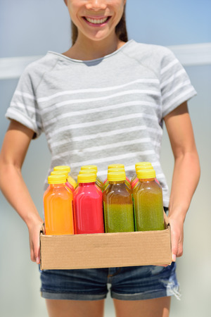 Juice detox - cleanse diet with juicing raw and organic fruits and veggies. Fresh juices delivery woman with vegetable drinks. Young girl carrying a box of juice bottles.
