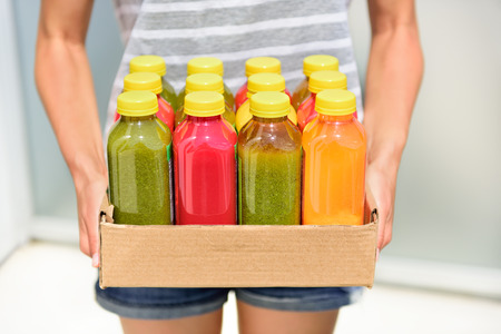 Juicing cold pressed vegetable juices for a detox diet. Dieting by cleansing your body from toxins with raw organic fruits and vegetables juice made fresh and delivered in bottles. Stok Fotoğraf - 40338582