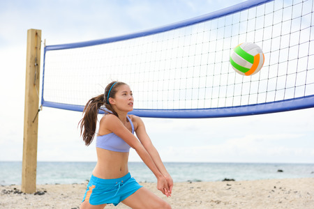 beach volley: Beach volleyball woman playing game hitting forearm pass volley ball during match on summer beach. Female model living healthy active lifestyle doing sport on beach.