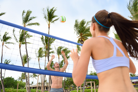 beach volleyball: People playing beach volleyball having fun in sporty active lifestyle. Man hitting volley ball in game in summer. Woman and man fitness model living healthy lifestyle doing sport on beach.