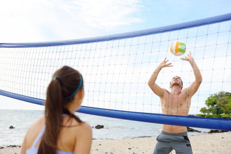 female volleyball: People playing beach volleyball having fun in sporty active lifestyle. Man hitting volley ball in game in summer. Woman and man fitness model living healthy lifestyle doing sport on beach.