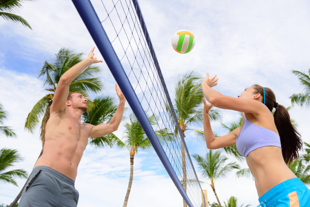 beach volleyball: Friends playing beach volleyball sport. Woman and man having fun recreational volley ball game in summer living healthy active sport lifestyle.