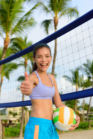 Happy beach volleyball woman player thumbs up. Excited smiling woman holding beach volley ball giving thumbs up success hand sign looking at camera. Mixed race Asian Caucasian woman athlete.