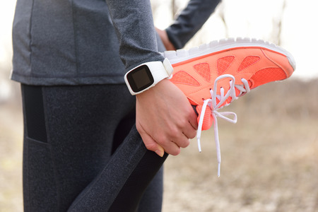 training shoes: Running stretching - runner wearing smartwatch. Closeup of running shoes, woman stretching leg as warm-up before run with sport activity tracker watch at wrist to monitor the heart rate during cardio.