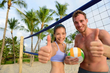 Happy beach volleyball players thumbs up. Excited smiling man and woman with beach volley ball giving thumbs up success hand sign looking at camera. Asian woman, Caucasian man.