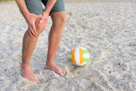 sprained joint: Injuries - sports knee injury on man playing beach volleyball. Male beach volley ball player with pain, maybe from sprain knee. Close up of legs, muscle and knee outdoors.
