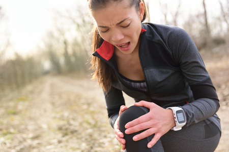 human knee: Sport and fitness injury - Female runner with hurting knee. Running woman screaming in pain during run wearing a smartwatch. Painful joint during workout.