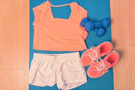 Sportkleding - fitness outfit en loopschoenen. Overhead van kleding klaar voor het heffen van gewichten in de sportschool of thuis, tot op een yoga mat op de grond. Passende t-shirt en sneakers oranje. Stockfoto