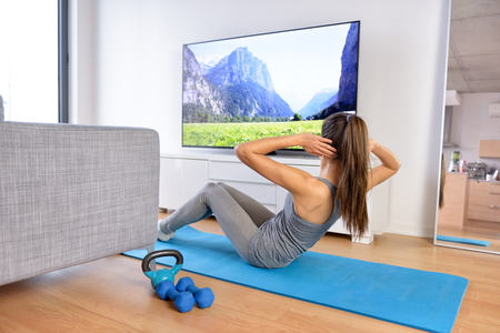 Home workout - woman exercising in front of a flat screen watching a fitness program or exercising during a TV show lying on a yoga mat in front of the sofa in the living room of a house or apartment. Stock Photo