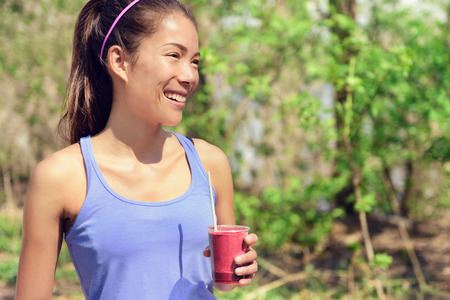 Healthy Asian woman drinking fruit smoothie drink in outdoor forest park during summer. Young fit girl holding plastic cup clean eating for detox cleansing with berry or beet juice as part of a diet. Stock Photo