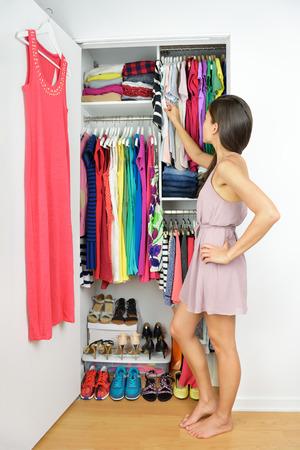 Startseite Schrank - Frau, die Wahl ihrer Modekleidung. Shopping-Konzept. Frau, die viele neue Kleider mit Blick auf Unentschlossenheit vor vielen Möglichkeiten von stilvollen Kleider und Röcke in organisierten sauber walk-in.