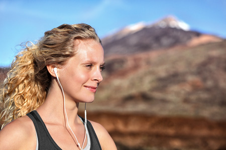 blonde girls: Running girl with earphones - woman runner listening to music in earbuds. Female athlete portrait after running in beautiful nature. Healthy lifestyle concept with beautiful young blonde fitness model
