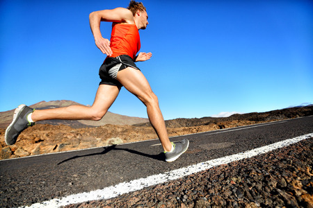 Runner man running sprinting for success on run. Male athlete runner training at fast speed. Muscular fit sport model sprinter exercising sprint on mountain road. Full body length of Caucasian model. Stock Photo