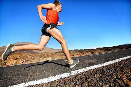 Runner man running sprinting for success on run. Male athlete runner training at fast speed. Muscular fit sport model sprinter exercising sprint on mountain road. Full body length of Caucasian model. Archivio Fotografico