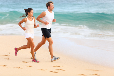 buddies: Running couple jogging on beach exercising and jogging training. Sport runners working out on summer beach. Asian woman, Caucasian man. Stock Photo