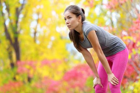 sudando: Atleta corredor de descanso después de correr - mujer asiática. y trotar entrenamiento al aire libre en el bosque. Cansado modelo de la aptitud deportiva hermosa agotado vivir el estilo de vida saludable y activo. Raza mixta asiática caucásica. Foto de archivo