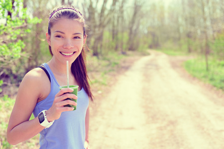 workout: Healthy fitness girl drinking green spinach vegetable smoothie wearing smartwatch heart rate monitor during outdoor running workout in forest park during summer or spring. Happy fit Asian woman. Stock Photo