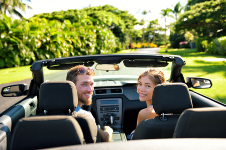 Happy couple in car on summer road trip travel. Multiracial young couple carefree on holidays driving a convertible cabriolet automobile on the roadway in the city looking back at camera.